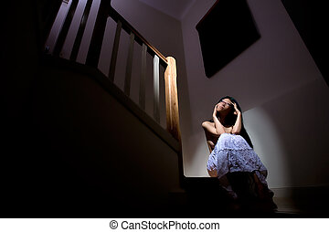 Lonesome woman - Beautiful girl sits alone on stairs in dark...