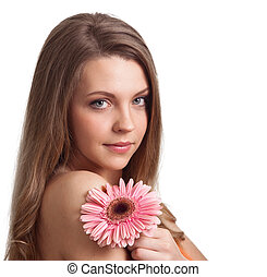 closeup of a pretty young woman smelling a pink flower