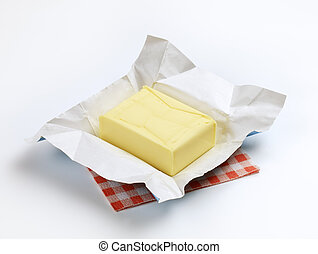 Fresh butter - Block of fresh butter resting on a wrapper