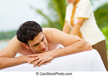 Man At Spa - An attractive young man enjoying a back massage...