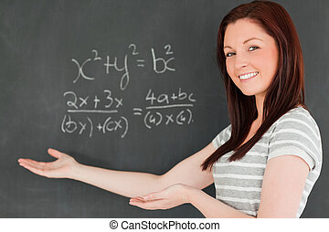 Beautiful young woman showing an equation on a blackboard in...