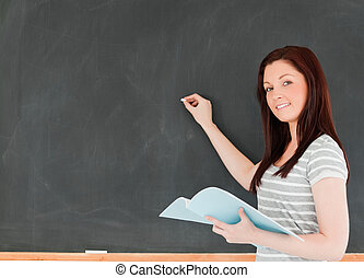 Young woman about to write on a blackboard looking at the camera in a classroom