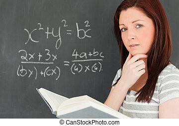 Reflective young woman trying to solve an equation