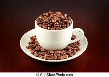 Cup of coffee filled up with coffee beans on dark brown...