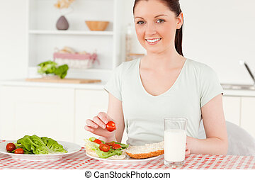 Attractive woman ready to eat a sandwich for lunch in her...