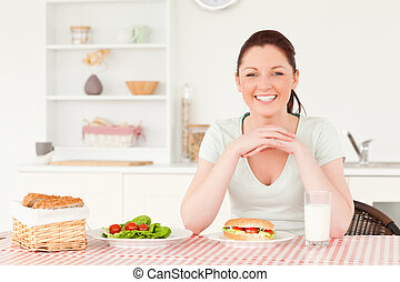 Good looking woman ready to eat a sandwich for lunch
