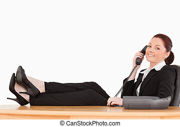 Good looking businesswoman on the phone in her office...