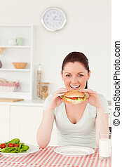 Beautiful woman eating a sandwich for lunch