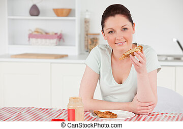 Beautiful woman posing while eating a slice of bread