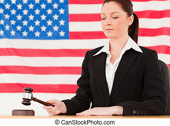 Serious young judge knocking a gavel