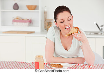 Attractive woman posing while eating a slice of bread