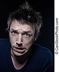 Funny Man Portrait grimacing - studio portrait on black...