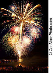 Brightly colorful fireworks in the night sky - Brightly...