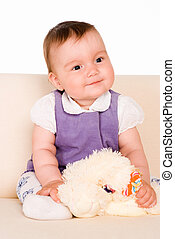 nice baby on sofa - cute little baby sitting on a sofa