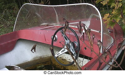 Abandoned red motorboat. Closeup. - An abandoned boat sits...