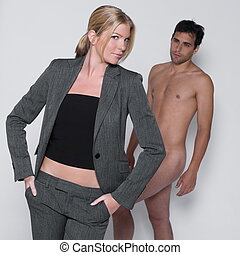 young couple with man naked in studio on isolated grey...