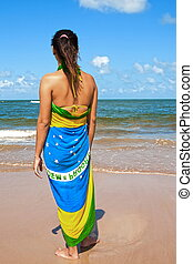 woman with the brazilian flag sarong on the beach looking at...