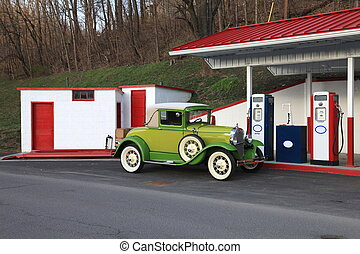 Vintage car at retro gas station - Old car fueling up for at...