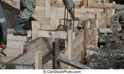 Worker pours the foundation of building