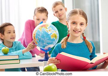 Smart reader - Cute schoolgirl with open book looking at...