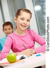 Pretty pupil - Portrait of smart schoolgirl making notes and...