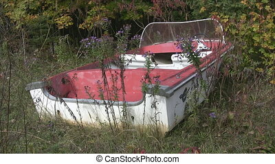 Abandoned red boat. Medium shot. - An abandoned boat sits in...