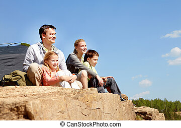 Campers on cliff - Portrait of family of travelers sitting...