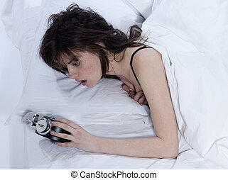 woman in bed awakening - young woman in a white sheet bed on...