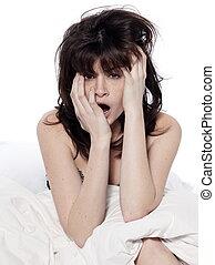 woman in bed awakening yawning - young woman awakening...