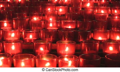 Lots of red church candles. - Many red votive candles from a...