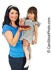 Mother with daughter eating fruit tart - Mother holding her...