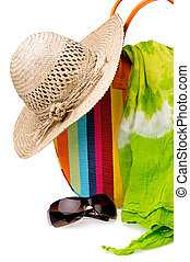 Beach items: colorful striped bag, straw hat, sunglasses and...