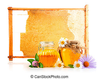 sweet honey in glass jars and honeycomb with  flowers