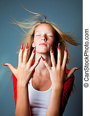 blonde girl with closed eyes and hair fluttering on wind hiding shows beautiful hands with long fingers and fashionable design of nails on dark blue background