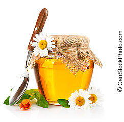 sweet honey in glass jar with spoon and flowers