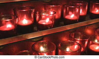 Red church candles on gold shelves.