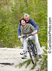 Happy leisure - Portrait of happy mature couple riding...