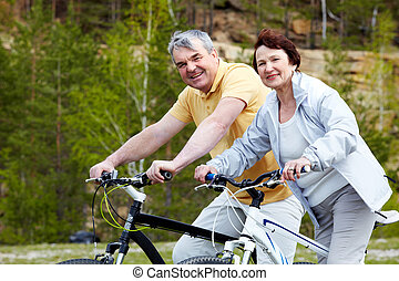 People on bicycles - Portrait of happy mature couple on...