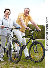 Cycling couple - Portrait of happy mature couple on bicycles...