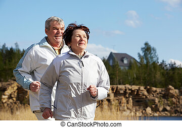 People running - Portrait of happy mature couple running...