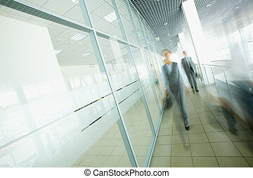 Businesspeople walking - Blurred businesspeople moving in...