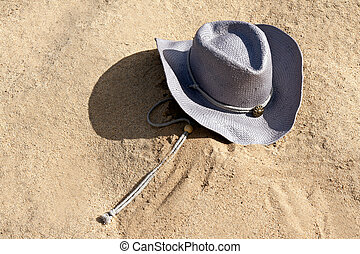 purple hat with a strap on the sand under the sun