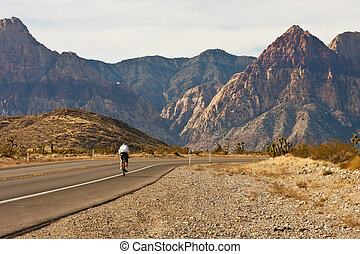 Cyclist on Road Through Desert Into Mountains - A lone...