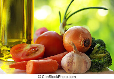 Olive oil and vegetables in green background.