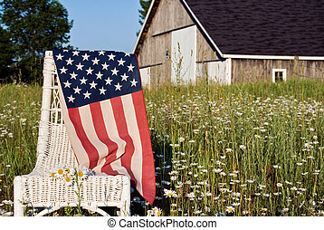 American flag on chair in daisy field.