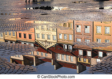 Warsaw, Poland. Old Town rain puddle reflection - tenements...
