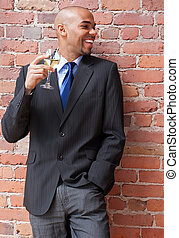 Laughing young businessman with a glass of wine - Laughing...