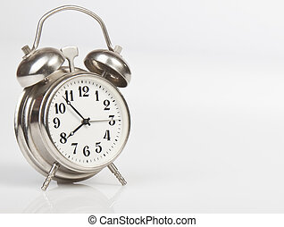 Metal alarm clock on a black background for your design