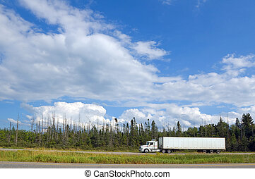 Cargo truck on Canada Highway under cloud blue sky