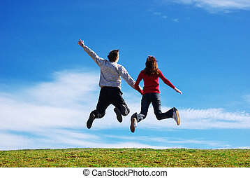 Couple jump in the meadow